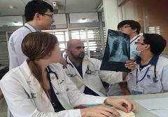 Physicians examining a lung x-ray