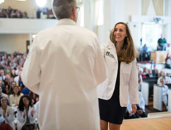 Dean page shaking student's hand at White Coat 2019