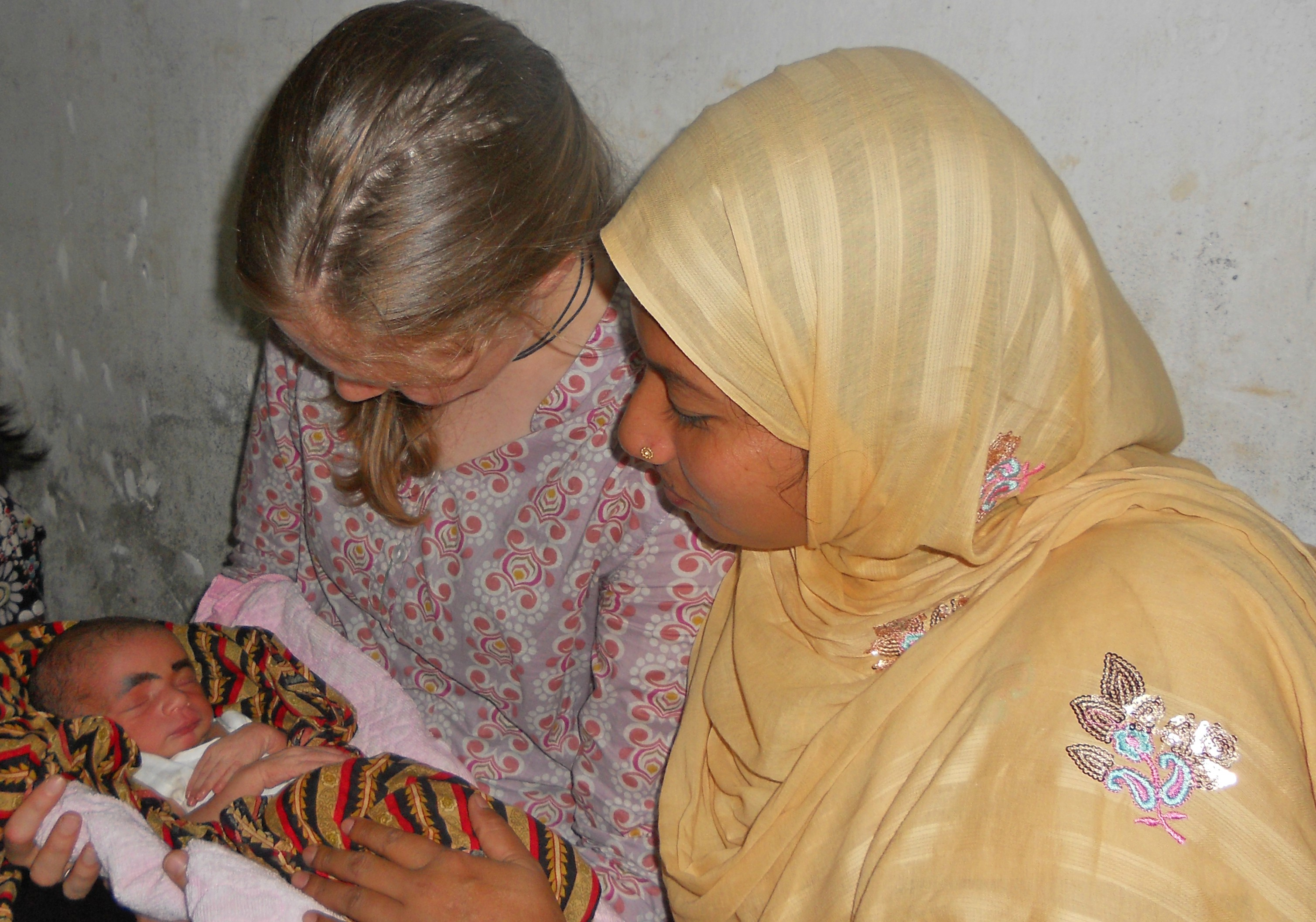 VTC Researcher in Bangladesh holding baby with mother