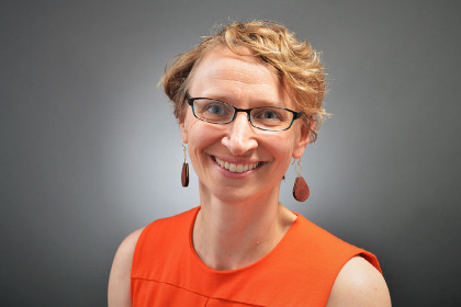 Photo of Christa Zehle, M.D., in an orange dress against a dark background