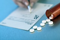 Image of a prescription being written next to a bottle of pills
