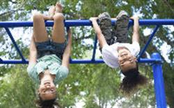 Two children upside down on the monkey bars
