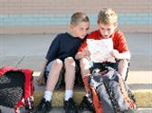 Two boys with backpacks sit on sidewalk and go over homework