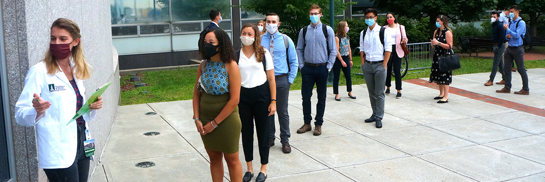 Students line up with masks, 6 feet apart, for orientation