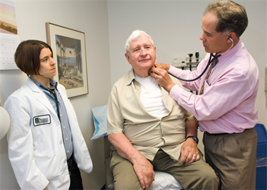 Photo of a physician precepting a student with patient
