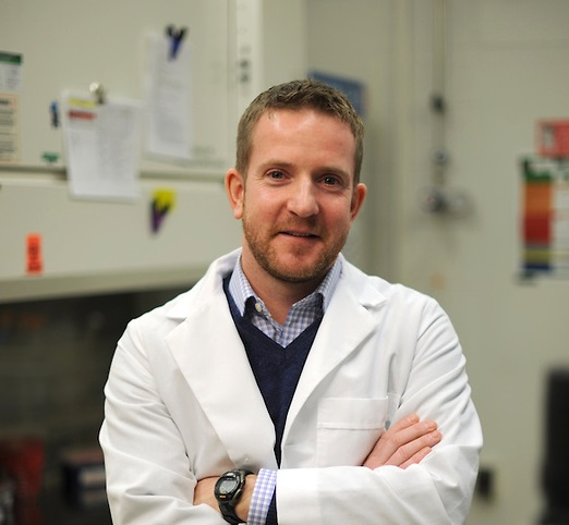 Sean Diehl, PhD in lab coat smiling