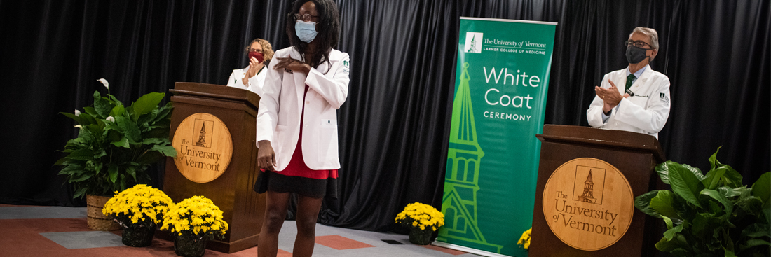 A student puts on her white coat at the white coat ceremony